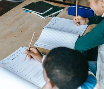crop ethnic schoolkids with tasks at desk