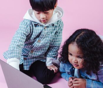 content diverse little friends watching video on laptop