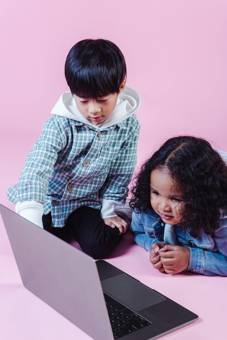 content diverse little friends watching video on laptop